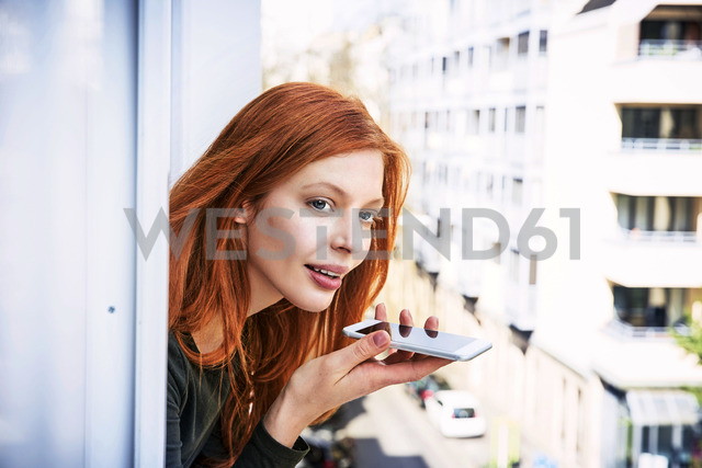 Portrait of redheaded woman on the phone leaning out of window - FMKF04864