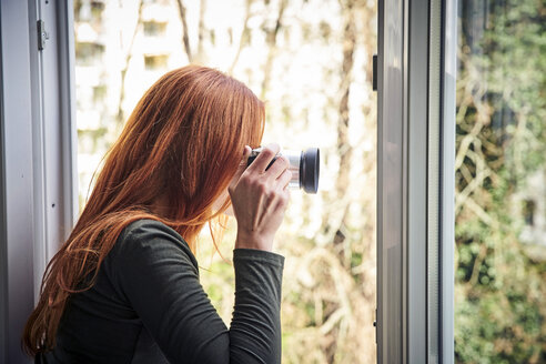 Redheaded woman leaning out of window taking photo with camera - FMKF04867