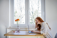 Laughing redheaded woman sitting at table in front of window using laptop - FMKF04870