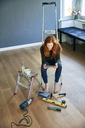 Redheaded woman sitting on step ladder using tablet - FMKF04876