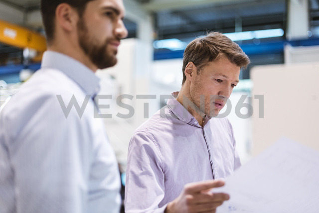 Two men in factory looking at plan - DIGF03429