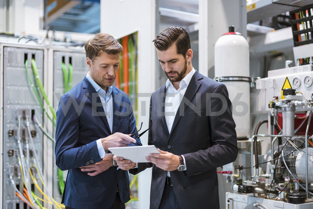 Two businessmen in factory looking at tablet - DIGF03438
