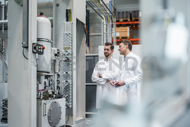 Two men wearing lab coats in factory looking at machine - DIGF03444