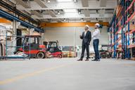 Two men wearing hard hats in factory shop floor - DIGF03447