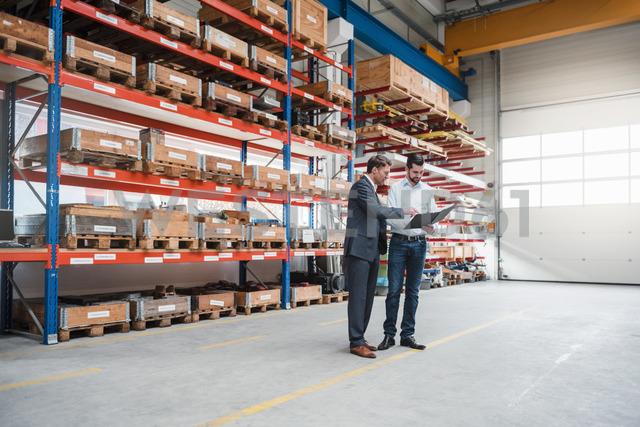Two men walking and talking in factory shop floor - DIGF03450