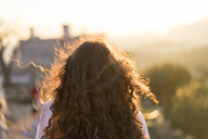 Back view of young woman with long curly hair at sunset - AFVF00115