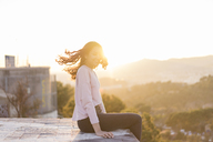 Young woman sitting on a wall at sunset tossing her hair - AFVF00118