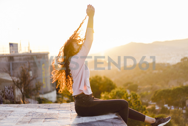 Young woman sitting on a wall at sunset pulling her hair - AFVF00121