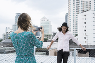 Young woman with smartphone taking picture of boyfriend on rooftop - SBOF01377