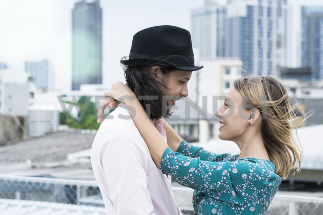 Young affectionate couple standing on rooftop - SBOF01380