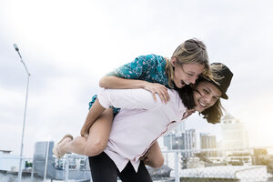 Young affectionate couple having fun together on rooftop - SBOF01383