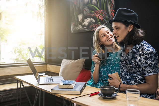 Artist couple sitting in cafe and having fun together - SBOF01395