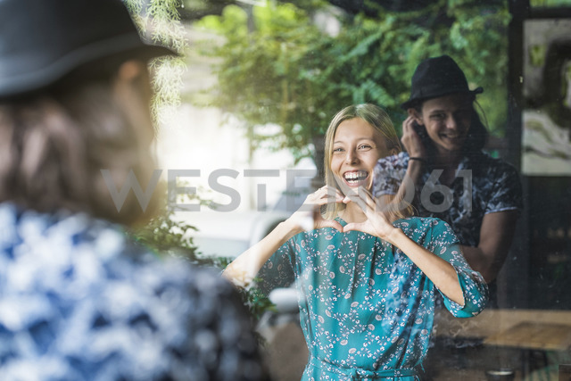 Beautiful young woman making a finger frame heart and smiling at her boyfriend through a window - SBOF01398