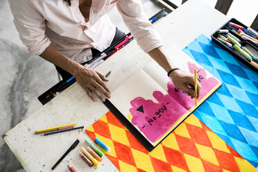 Artist's hands drawing into notebook with his artwork on the table - SBOF01407
