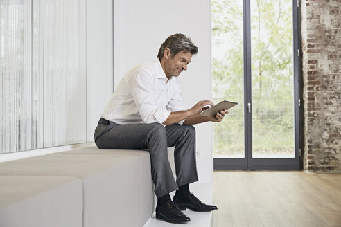 Businessman sitting on bench in modern office using tablet - PDF01449