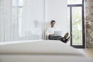 Businessman sitting on bench in modern office using laptop - PDF01458