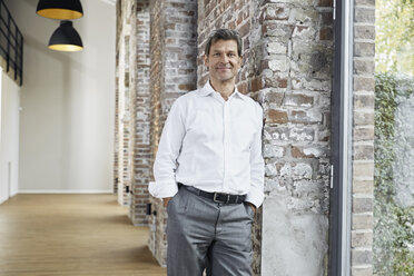 Portrait of smiling businessman leaning against brick wall in modern office - PDF01467