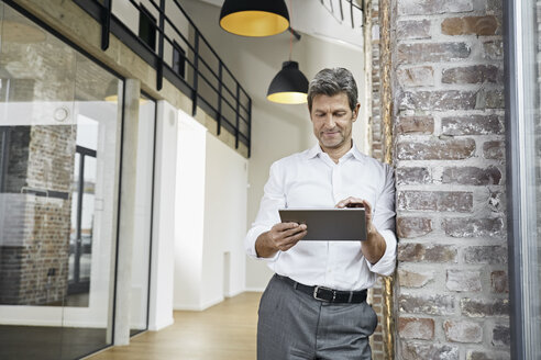 Portrait of mature businessman using tablet in modern office - PDF01470