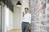 Mature businessman using smartphone in modern office - PDF01473