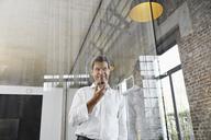 Mature businessman using smartphone in modern office - PDF01488