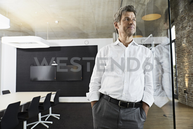Portrait of mature businessman leaning against glass pane in modern conference room - PDF01491