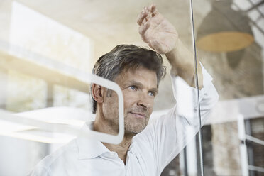Portrait of mature businessman leaning against glass wall in office - PDF01494