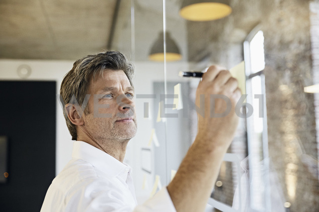 Mature businessman writing on sticky notes at glass pane in office - PDF01497