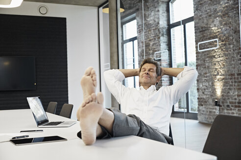 Barefooted businessman relaxing in conference room of modern office - PDF01506