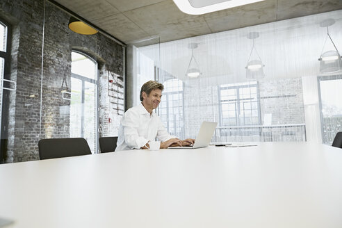 Mature businessman in bright modern conference room using laptop - PDF01509