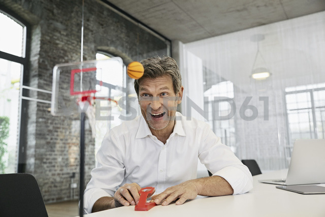Happy businessman playing mini basketball game in modern office - PDF01512 - Philipp Dimitri/Westend61