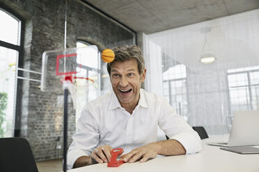 Happy businessman playing mini basketball game in modern office - PDF01512
