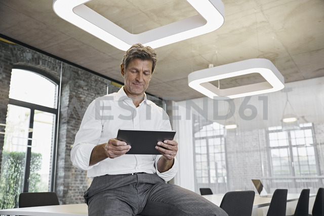 Mature businessman using tablet in modern office - PDF01515