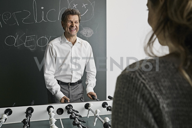Businessman playing foosball with female colleague - PDF01521