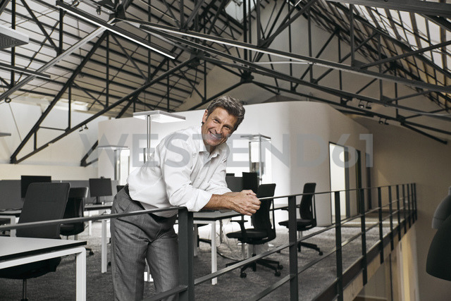 Portrait of smiling mature businessman on gallery in modern office - PDF01542