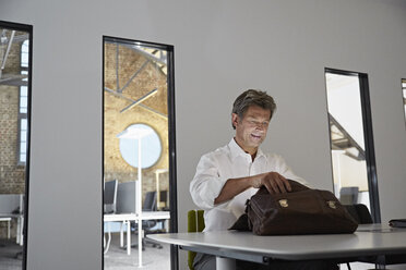 Businessman looking in shining briefcase in conference room of modern office - PDF01545
