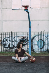 Young woman sitting with basketball on outdoor court - VPIF00330