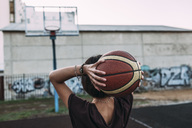 Rear view of young woman holding basketball on outdoor court - VPIF00333