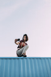 Young woman with basketball taking a selfie on container - VPIF00336