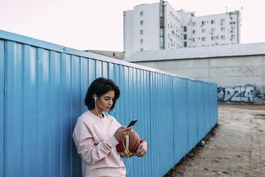 Young woman with basketball, smartphone and earphones at container - VPIF00339
