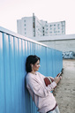Young woman with basketball, smartphone and earphones at container - VPIF00342