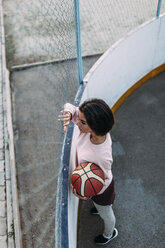 Young woman standing with basketball at fence - VPIF00345