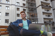 Redheaded young man sitting on bench with laptop - VPIF00351