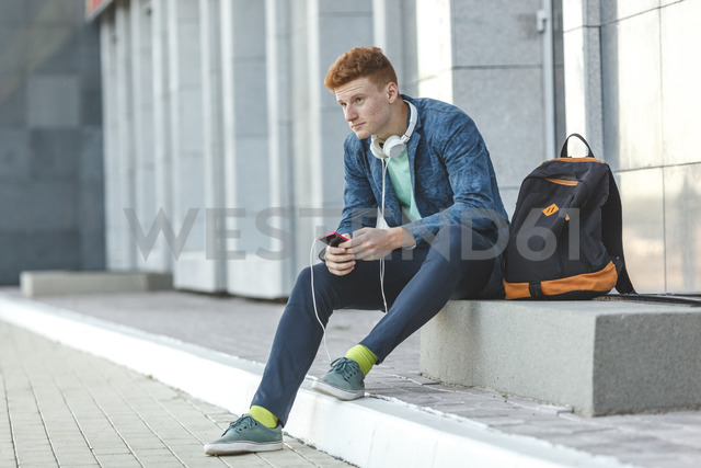 Redheaded young man sitting outdoors with smartphone and headphones - VPIF00354