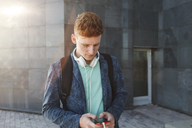 Redheaded young man outdoors with smartphone and headphones - VPIF00357