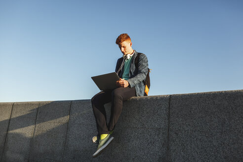 Redheaded young man sitting on wall using laptop - VPIF00363
