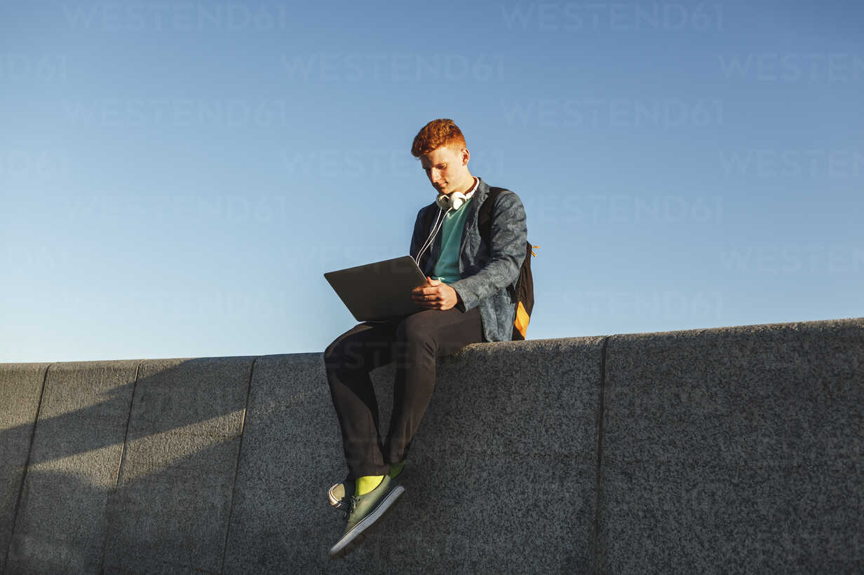 Redheaded young man sitting on wall using laptop - VPIF00363 - Vasily Pindyurin/Westend61