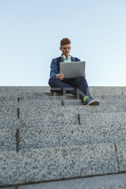 Redheaded young man sitting on stairs using laptop - VPIF00366