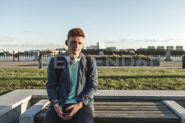 Portrait of redheaded young man sitting on bench with smartphone and headphones - VPIF00369