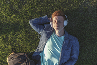 Redheaded young man with headphones lying on grass - VPIF00372