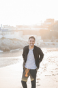 Portrait of laughing young man on the beach at twilight - AFVF00135